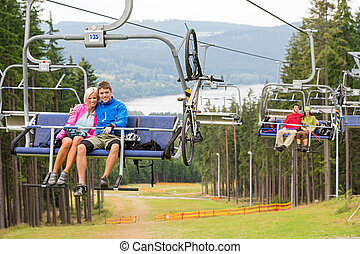 Smiling couples using chair lift scenic landscape - Smiling...