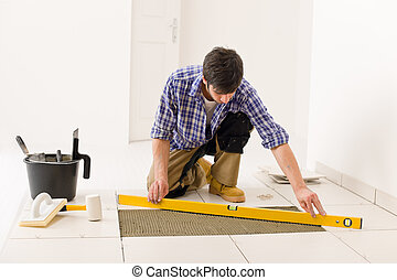 Home tile improvement - handyman with level laying down tile...