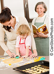 Little girl with mother cutting out cookies in kitchen