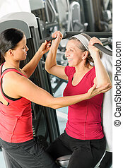 Personal trainer assist senior woman at gym - Personal...