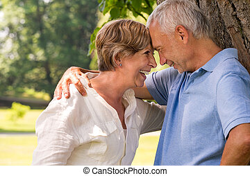 Elderly couple laughing head to head