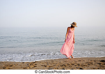 Beautiful woman with long pink dress on a tropical beach -...