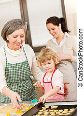 Little girl with grandmother cutting out cookies - Little...