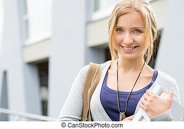 Young happy woman holding books to school smiling education...
