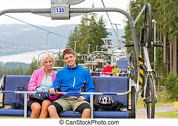Chair lift going through forest couple sitting - Chair lift...