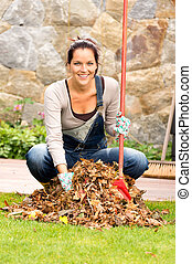 Cheerful woman sweeping leaves autumn pile backyard -...