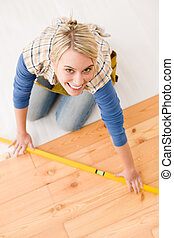 Home improvement - handywoman installing wooden floor - Home...