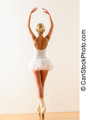 Ballerina pose from behind dancing in studio - Rear view of...