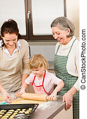 3 generations women rolling dough for baking - Happy little...