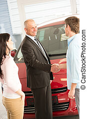 Couple buying a car in dealership - Young Caucasian couple...