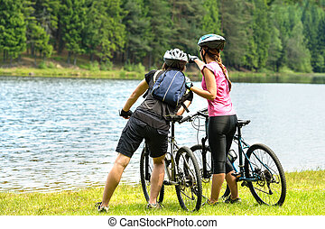Young bikers at lake watching the forest - Young bikers...