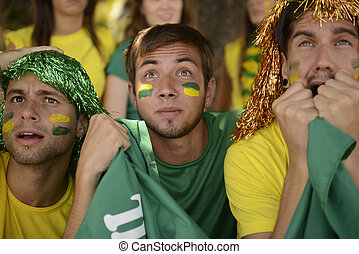Brazilian sport soccer fans looking at the screen. -...