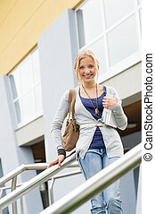 Teenage girl holding books to school smiling education...