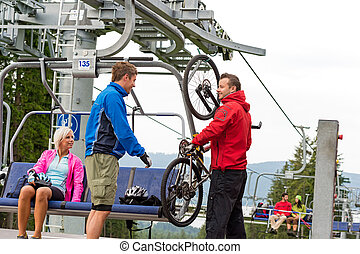 Man helping couple holding bicycle chair lift - Man helping...