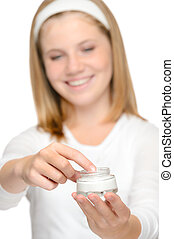 Smiling young girl applying moisturizer cream face