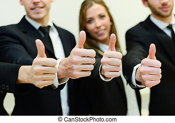 Business team holding their thumbs up - Close-up of business...
