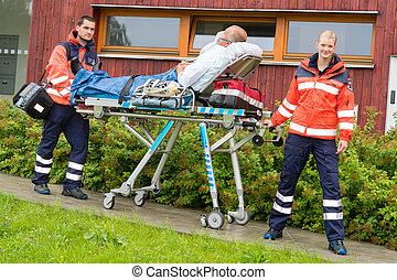 Paramedics with patient on stretcher ambulance aid -...