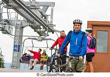Couple getting on bicycles chair lift trip - Sporty couple...