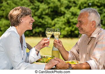 Elderly couple celebrating outdoors
