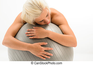 Tired sportive woman resting on fitness ball - Exhausted...