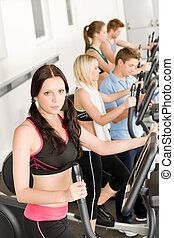 Fitness young group on elliptical cross trainer at health...