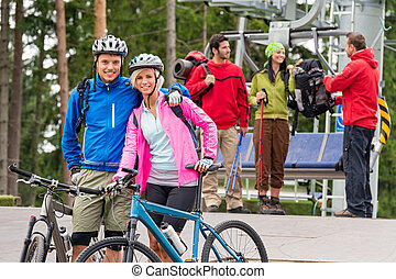 Mountain bikes couple and hikers after chair lift - Smiling...