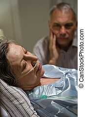 Dying woman in bed with caring man - Dying old woman in...