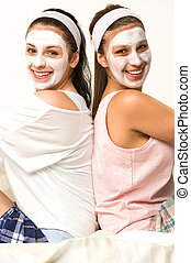 Two female friends with facial mask