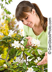 Gardening - Portrait of woman with Rhododendron flower on...
