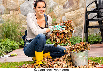 Woman putting leaves gardening cleaning bucket housework -...