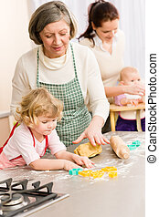 Little girl cutting dough for cookies - Grandmother with...