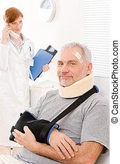 Senior patient broken arm in doctor office - Portrait of...