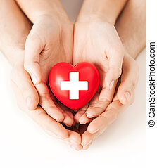 male and female hands with red heart - family health,...
