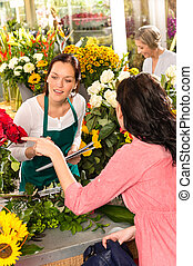 Young florist ordering roses woman customer flower market...