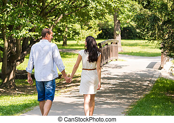 Rear view of walking couple in park