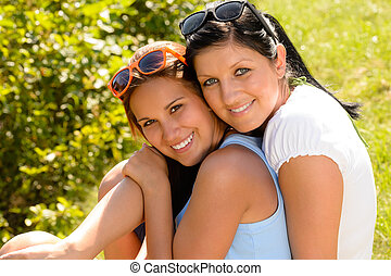 Mother and teen daughter hugging outdoors relaxing smiling...