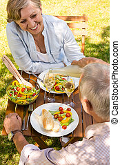 Retired couple eating and drinking outdoors - Smiling...