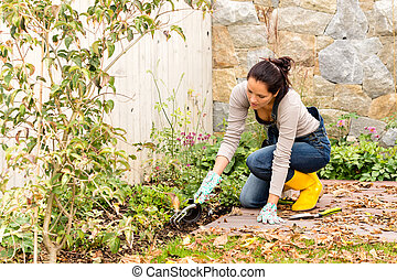 Young woman planting backyard gardening tools flowerbed -...