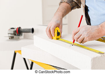 Home improvement - handyman measure porous brick in workshop