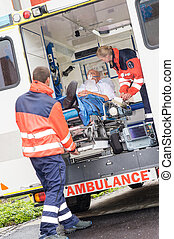 Paramedics putting patient in ambulance car aid - Paramedics...