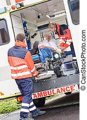 Paramedics putting patient in ambulance car aid - Paramedics...