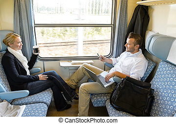 Man and woman sitting in train talking smiling commuters...