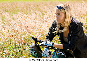 Mountain biking young woman sportive sunny meadows -...