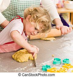 Little girl cutting dough for cookies - Little girl cutting...
