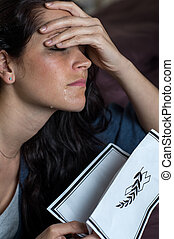 Crying young woman holding obituary - Portrait of crying...