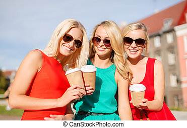 women with takeaway coffee cups in the city - holidays and...