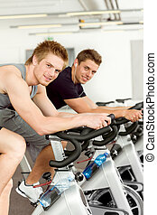 Fitness young man on gym bike spinning