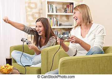 Students - Two female teenager playing video TV game in...