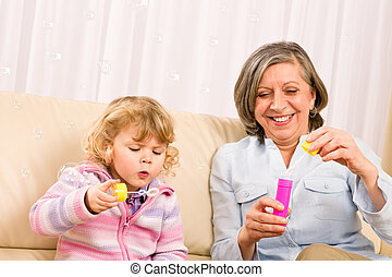 Little girl with grandmother play bubble blower - Little...