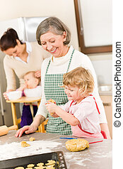Grandmother with little girl prepare dough for baking in...